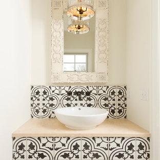 На фото: маленький туалет в средиземноморском стиле с настольной раковиной, столешницей из известняка, цементной плиткой, белыми стенами, полом из травертина, черно-белой плиткой и бежевой плиткой с