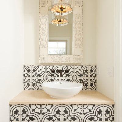 Inspiration for a small mediterranean cement tile, black and white tile and beige tile travertine floor powder room remodel in Minneapolis with a vessel sink, limestone countertops and white walls