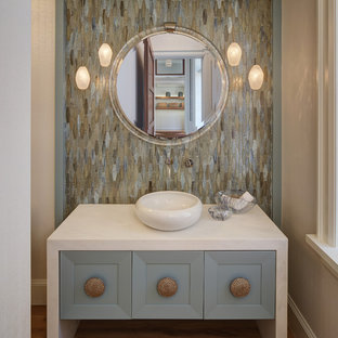 Medium sized nautical cloakroom in Miami with blue cabinets, multi-coloured tiles, a vessel sink, freestanding cabinets, mosaic tiles, marble worktops, medium hardwood flooring and white worktops.