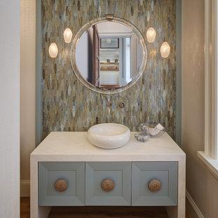 Modelo de aseo costero, de tamaño medio, con puertas de armario azules, baldosas y/o azulejos multicolor, lavabo sobreencimera, armarios tipo mueble, baldosas y/o azulejos en mosaico, encimera de mármol, suelo de madera en tonos medios y encimeras blancas