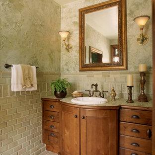 デンバーの中くらいのトラディショナルスタイルのおしゃれなトイレ・洗面所 (オーバーカウンターシンク、サブウェイタイル、家具調キャビネット、中間色木目調キャビネット、緑のタイル、緑の壁、セラミックタイルの床、御影石の洗面台、ベージュの床、グリーンの洗面カウンター) の写真