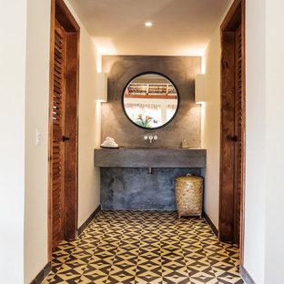На фото: маленький туалет в современном стиле с серой плиткой, цементной плиткой, бежевыми стенами, полом из керамогранита, врезной раковиной, столешницей из бетона и разноцветным полом