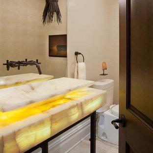 Modelo de aseo mediterráneo, de tamaño medio, con sanitario de dos piezas, paredes beige, suelo de piedra caliza, lavabo sobreencimera, encimera de ónix, suelo beige y encimeras amarillas