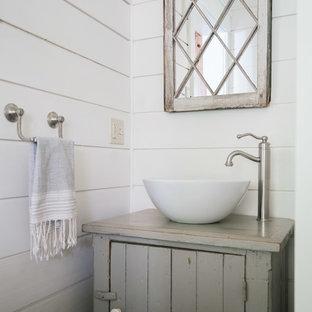 На фото: туалет в стиле кантри с фасадами островного типа, искусственно-состаренными фасадами, белыми стенами, настольной раковиной, столешницей из дерева и серой столешницей с
