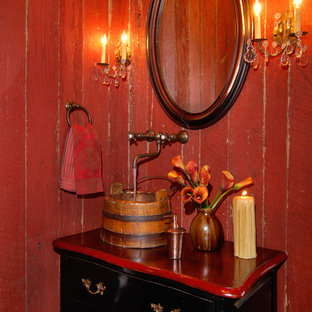 Photo of a small rustic cloakroom in Charlotte with a vessel sink, freestanding cabinets, black cabinets, wooden worktops, red walls, medium hardwood flooring and red worktops.