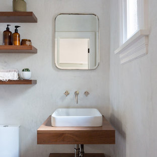 Powder room - small mediterranean powder room idea in Los Angeles with open cabinets, a vessel sink, wood countertops and beige walls