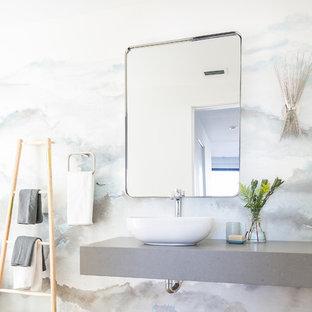 Immagine di un bagno di servizio moderno di medie dimensioni con nessun'anta, WC monopezzo, pareti grigie, pavimento con piastrelle in ceramica, lavabo a bacinella, top in superficie solida e pavimento beige
