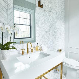 ニューヨークの小さいトランジショナルスタイルのおしゃれなトイレ・洗面所 (グレーのタイル、大理石タイル、グレーの壁、コンソール型シンク、白い洗面カウンター) の写真