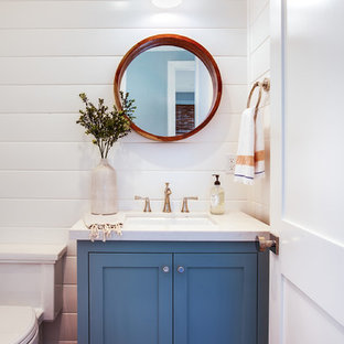 This is an example of a small coastal cloakroom in Los Angeles with shaker cabinets, blue cabinets, white walls, dark hardwood flooring, a wall-mounted sink, engineered stone worktops, brown floors and white worktops.