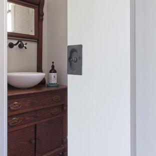 Réalisation d'un WC et toilettes champêtre de taille moyenne avec un placard en trompe-l'oeil, des portes de placard en bois sombre, un sol en brique, une vasque, un plan de toilette en bois et un sol rouge.