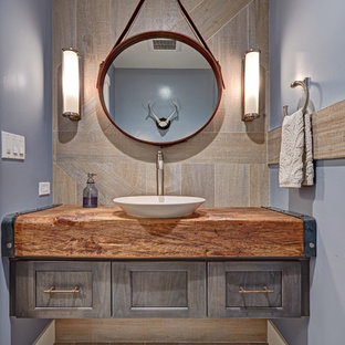 Inspiration for a small cottage gray tile and porcelain tile porcelain floor powder room remodel in Sacramento with a vessel sink, recessed-panel cabinets, gray cabinets, wood countertops, blue walls and brown countertops