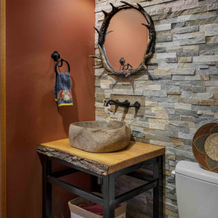 Design ideas for a small rustic cloakroom in Burlington with black cabinets, wooden worktops, open cabinets, a two-piece toilet, multi-coloured tiles, orange walls, a vessel sink, multi-coloured floors and a freestanding vanity unit.
