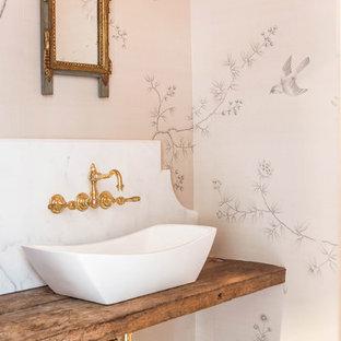 Exemple d'un WC et toilettes victorien avec une vasque, un plan de toilette en bois, un mur beige et un plan de toilette marron.