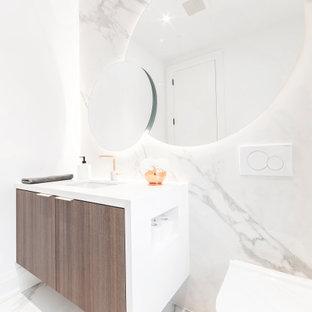 На фото: огромный туалет в современном стиле с плоскими фасадами, фасадами цвета дерева среднего тона, инсталляцией, белой плиткой, керамогранитной плиткой, белыми стенами, полом из керамогранита, врезной раковиной, столешницей из искусственного кварца, белым полом и белой столешницей с