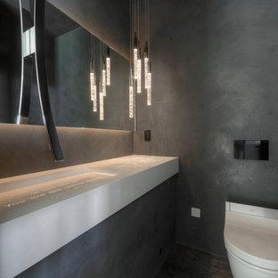 Пример оригинального дизайна: туалет среднего размера в современном стиле с инсталляцией, серой плиткой, керамической плиткой, серыми стенами, полом из керамической плитки, подвесной раковиной, серым полом и белой столешницей