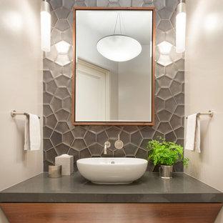 На фото: туалеты в современном стиле с серой плиткой, белыми стенами, настольной раковиной и серой столешницей
