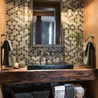 На фото: туалет в стиле рустика с фасадами цвета дерева среднего тона, разноцветной плиткой, столешницей из дерева и накладной раковиной с