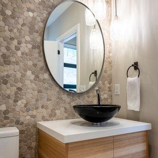 Kleine Moderne Gästetoilette mit flächenbündigen Schrankfronten, hellen Holzschränken, Toilette mit Aufsatzspülkasten, beigefarbenen Fliesen, Kieselfliesen, beiger Wandfarbe, Kiesel-Bodenfliesen, Aufsatzwaschbecken, Quarzwerkstein-Waschtisch, beigem Boden und weißer Waschtischplatte in Sonstige