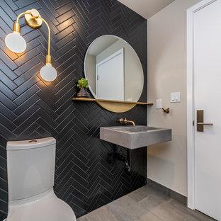 50 tals inredning av ett litet grå grått toalett, med en toalettstol med separat cisternkåpa, svart kakel, keramikplattor, svarta väggar, klinkergolv i porslin, ett integrerad handfat, bänkskiva i betong och grått golv
