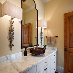 This is an example of a medium sized traditional cloakroom in New Orleans with a vessel sink, beaded cabinets, white cabinets, marble worktops, yellow walls and white worktops.