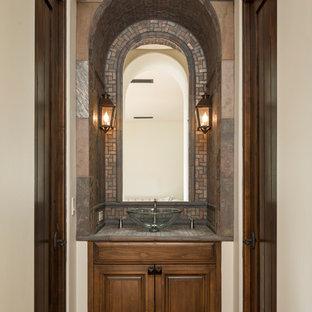 Esempio di un bagno di servizio mediterraneo con lavabo a bacinella, ante con bugna sagomata, ante in legno bruno, piastrelle grigie, piastrelle a mosaico, pavimento in terracotta e pareti beige
