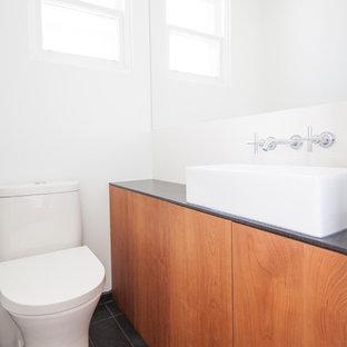 Réalisation d'un petit WC et toilettes minimaliste avec un placard à porte plane, des portes de placard en bois brun, un WC à poser, un carrelage blanc, des carreaux de céramique, un mur blanc, un sol en ardoise, une vasque, un plan de toilette en granite, un sol noir et un plan de toilette noir.