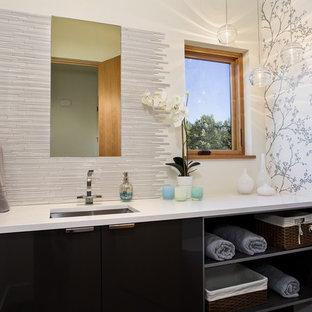 Неиссякаемый источник вдохновения для домашнего уюта: туалет в современном стиле с врезной раковиной, плоскими фасадами, черными фасадами, удлиненной плиткой, белой плиткой и белой столешницей