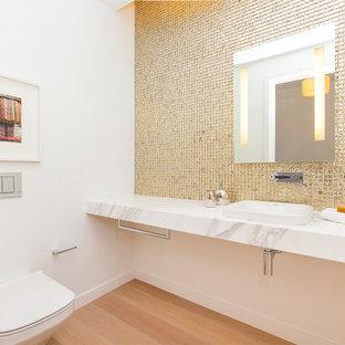 Modelo de aseo contemporáneo, de tamaño medio, con sanitario de pared, paredes blancas, suelo de madera clara, lavabo encastrado, encimera de mármol, baldosas y/o azulejos de metal y suelo beige