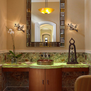 Inspiration for a mediterranean cloakroom in Miami with a vessel sink, flat-panel cabinets, medium wood cabinets, glass worktops, multi-coloured tiles, stone tiles, beige walls, marble flooring and green worktops.