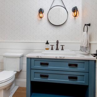 トロントの中くらいのトランジショナルスタイルのおしゃれなトイレ・洗面所 (シェーカースタイル扉のキャビネット、青いキャビネット、分離型トイレ、白い壁、淡色無垢フローリング、マルチカラーの洗面カウンター、独立型洗面台、塗装板張りの壁、羽目板の壁、壁紙) の写真