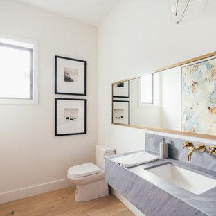 ロサンゼルスのビーチスタイルのおしゃれなトイレ・洗面所 (白い壁、無垢フローリング、アンダーカウンター洗面器、茶色い床、グレーの洗面カウンター、三角天井) の写真