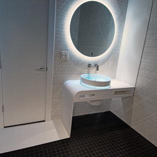 Cette image montre un petit WC et toilettes minimaliste avec des portes de placard blanches, un bidet, un carrelage noir et blanc, des carreaux de céramique, un mur noir, un sol en carrelage de terre cuite, une vasque, un plan de toilette en surface solide, un sol noir, un plan de toilette blanc et meuble-lavabo encastré.
