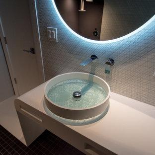 Aménagement d'un petit WC et toilettes moderne avec des portes de placard blanches, un bidet, un carrelage noir et blanc, des carreaux de céramique, un mur noir, un sol en carrelage de terre cuite, une vasque, un plan de toilette en surface solide, un sol noir, un plan de toilette blanc et meuble-lavabo encastré.