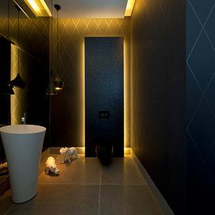 Свежая идея для дизайна: большой туалет в стиле модернизм с настольной раковиной, инсталляцией, черными стенами и полом из известняка - отличное фото интерьера