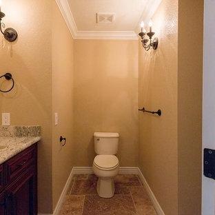 Idee per un bagno di servizio vittoriano di medie dimensioni con ante con bugna sagomata, ante in legno bruno, WC a due pezzi, pareti marroni, pavimento in travertino, lavabo sottopiano, top in granito, pavimento marrone e top grigio