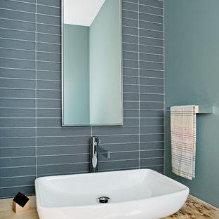 Пример оригинального дизайна: маленький туалет в современном стиле с серой плиткой, стеклянной плиткой, зелеными стенами, настольной раковиной и столешницей из дерева