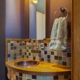 This is an example of a small eclectic cloakroom in Other with multi-coloured tiles, ceramic tiles, purple walls, a built-in sink and wooden worktops.