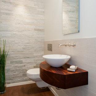 Cette photo montre un petit WC et toilettes chic avec des portes de placard en bois sombre, un WC suspendu, un carrelage blanc, un carrelage de pierre, un mur blanc, un sol en liège et une vasque.