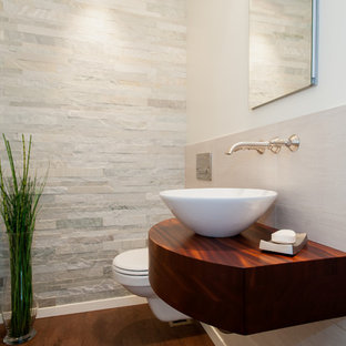 Idéer för små vintage toaletter, med skåp i mörkt trä, en vägghängd toalettstol, stenkakel, vita väggar, korkgolv, ett fristående handfat och grå kakel