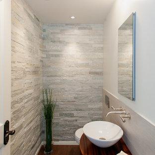 Inspiration pour un petit WC et toilettes traditionnel avec un WC suspendu, un carrelage de pierre, un mur blanc, un sol en liège, une vasque et un carrelage gris.
