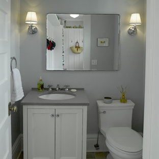 Small traditional cloakroom in New York with flat-panel cabinets, white cabinets, a one-piece toilet, grey tiles, grey walls, slate flooring, a submerged sink and engineered stone worktops.
