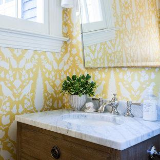 シアトルの小さいトランジショナルスタイルのおしゃれなトイレ・洗面所 (家具調キャビネット、中間色木目調キャビネット、分離型トイレ、黄色い壁、濃色無垢フローリング、アンダーカウンター洗面器、大理石の洗面台、白い洗面カウンター) の写真