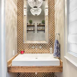 На фото: туалеты в стиле современная классика с бежевыми стенами, настольной раковиной, столешницей из дерева, паркетным полом среднего тона и коричневой столешницей