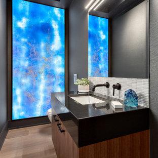 Kleine Maritime Gästetoilette mit flächenbündigen Schrankfronten, dunklen Holzschränken, Toilette mit Aufsatzspülkasten, schwarzer Wandfarbe, braunem Holzboden, Unterbauwaschbecken, Quarzwerkstein-Waschtisch, schwarzer Waschtischplatte, schwebendem Waschtisch und Kassettendecke in Vancouver