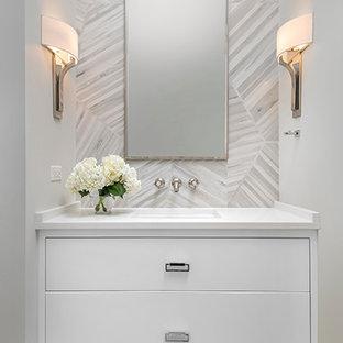 Cette image montre un WC et toilettes traditionnel de taille moyenne avec un placard à porte plane, des portes de placard blanches, un WC suspendu, un carrelage gris, des carreaux de porcelaine, un mur gris, un sol en carrelage de porcelaine, un lavabo encastré et un plan de toilette en quartz modifié.