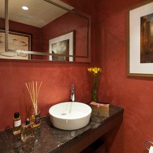 На фото: маленький туалет в современном стиле с настольной раковиной, темными деревянными фасадами, столешницей из гранита, унитазом-моноблоком, разноцветной плиткой, красными стенами и полом из керамогранита с