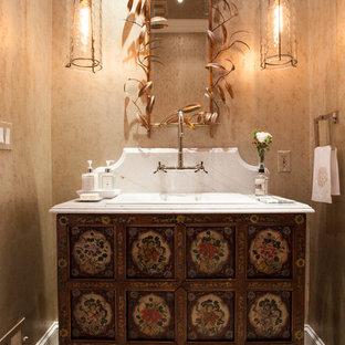 Пример оригинального дизайна: туалет среднего размера в стиле современная классика с фасадами островного типа, бежевыми стенами, полом из известняка, мраморной столешницей и накладной раковиной