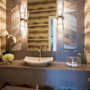 Стильный дизайн: большой туалет в современном стиле с настольной раковиной, столешницей из дерева, разноцветной плиткой, коричневыми стенами, светлым паркетным полом, плиткой из листового камня и серой столешницей - последний тренд