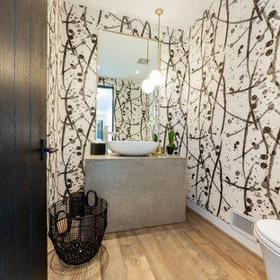 Идея дизайна: маленький туалет в современном стиле с столешницей из бетона, унитазом-моноблоком, разноцветными стенами, настольной раковиной и паркетным полом среднего тона