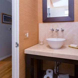 Cette photo montre un petit WC et toilettes bord de mer avec un placard sans porte, des portes de placard en bois sombre, un WC séparé, un mur beige, une vasque et un plan de toilette en travertin.
